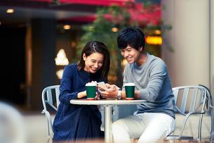 カフェでスマホを見る若い夫婦の写真素材 [FYI04269671]