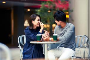 カフェでスマホを見る若い夫婦の写真素材 [FYI04269672]