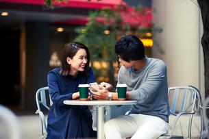 カフェでスマホを見る若い夫婦の写真素材 [FYI04269673]