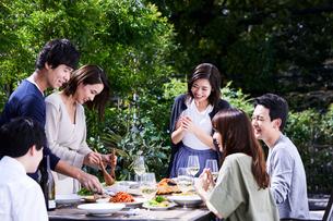 食事や飲み物をサーブする夫婦の写真素材 [FYI04269689]