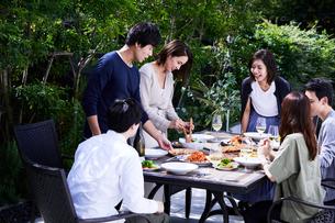 食事や飲み物をサーブする夫婦の写真素材 [FYI04269693]