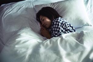 寝室のベッドで寝る若い女性の写真素材 [FYI04269724]