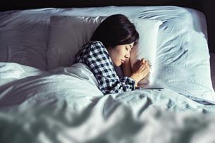 寝室のベッドで寝る若い女性の写真素材 [FYI04269726]