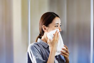 タオルで顔を拭いている女性の写真素材 [FYI04269734]