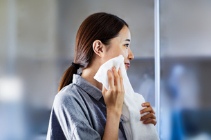 タオルで顔を拭いている女性の写真素材 [FYI04269737]