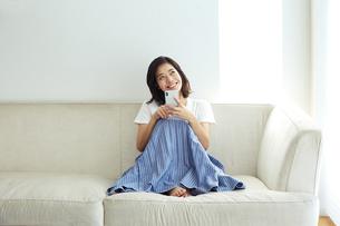 ソファでスマホを見る20代女性の写真素材 [FYI04269742]
