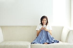 ソファでスマホを見る20代女性の写真素材 [FYI04269743]