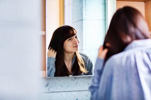 髪の毛にブラシを入れる20代女性の写真素材 [FYI04269746]