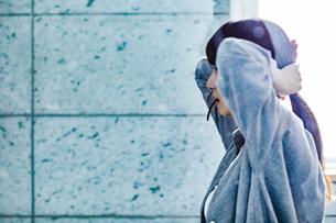 鏡の前で髪を束ねる20代女性の写真素材 [FYI04269749]