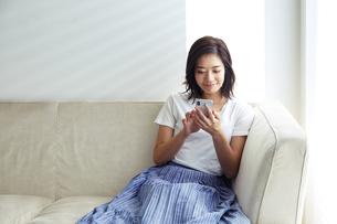 ソファでくつろぎながらスマホを見る20代女性の写真素材 [FYI04269751]