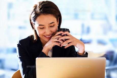 コーヒー飲みながらカフェで仕事をするビジネスウーマンの写真素材 [FYI04269752]