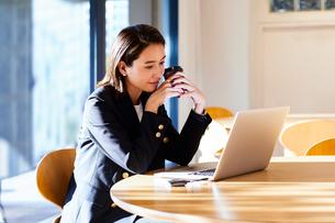 コーヒーを飲みながらカフェで仕事をするビジネスウーマンの写真素材 [FYI04269753]