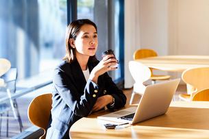 コーヒーを飲みながらカフェで仕事をするビジネスウーマンの写真素材 [FYI04269754]