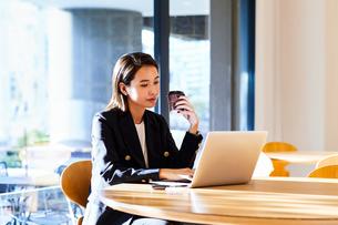 コーヒーを飲みながらカフェで仕事をするビジネスウーマンの写真素材 [FYI04269755]