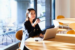 コーヒーを飲みながらカフェで仕事をするビジネスウーマンの写真素材 [FYI04269758]