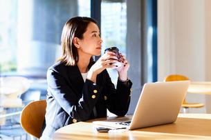 コーヒーを飲みながらカフェで仕事をするビジネスウーマンの写真素材 [FYI04269760]