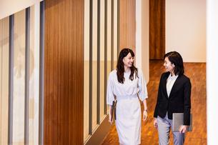 オフィスを会話しながら歩くビジネスウーマンの写真素材 [FYI04269764]