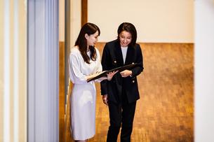 廊下で立ちながら打ち合わせをするビジネスウーマンの写真素材 [FYI04269767]