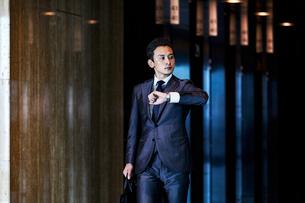 スーツ姿で腕時計を見るビジネスマンの写真素材 [FYI04269814]