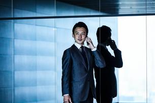 スーツ姿でスマホで電話するビジネスマンの写真素材 [FYI04269819]