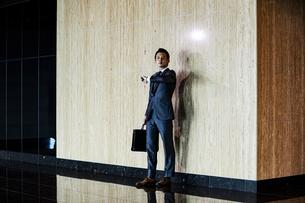 スーツ姿で腕時計を見るビジネスマンの写真素材 [FYI04269821]