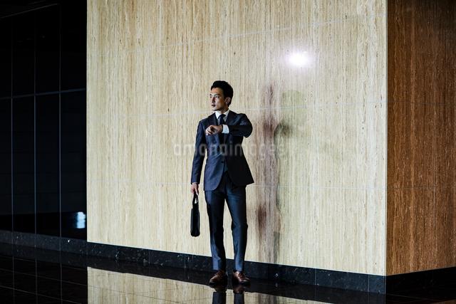 スーツ姿で腕時計を見るビジネスマンの写真素材 [FYI04269825]