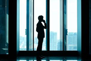 エレベーター前で電話するビジネスマンの写真素材 [FYI04269832]