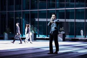 スーツ姿で電話しながら腕時計を見るビジネスマンの写真素材 [FYI04269840]