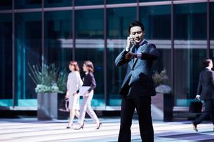 スーツ姿で電話しながら腕時計を見るビジネスマンの写真素材 [FYI04269843]
