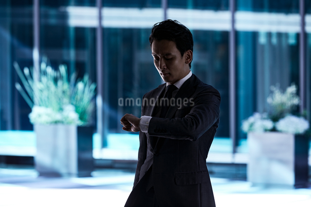 スーツ姿で腕時計を見るビジネスマンの写真素材 [FYI04269847]