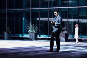 スーツ姿でスマホを見るビジネスマンの写真素材 [FYI04269848]
