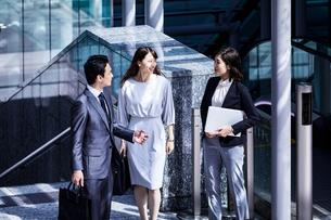 話しながらオフィスエリアを歩く男女の写真素材 [FYI04269851]