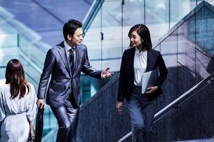 話しながらオフィスエリアを歩く男女の写真素材 [FYI04269853]