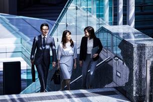 話しながらオフィスエリアを歩く男女の写真素材 [FYI04269854]