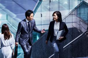 話しながらオフィスエリアを歩く男女の写真素材 [FYI04269855]