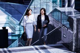 話しながらオフィスエリアを歩くビジネスウーマンの写真素材 [FYI04269856]