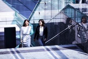 話しながらオフィスエリアを歩くビジネスウーマンの写真素材 [FYI04269858]