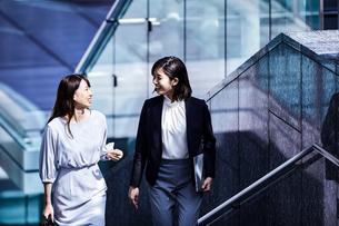 話しながらオフィスエリアを歩くビジネスウーマンの写真素材 [FYI04269859]