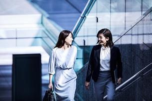 話しながらオフィスエリアを歩くビジネスウーマンの写真素材 [FYI04269860]