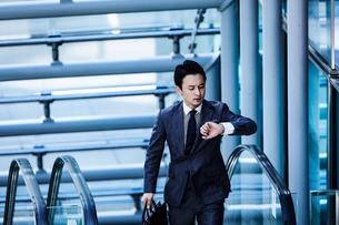 スーツ姿で腕時計を見るビジネスマンの写真素材 [FYI04269861]