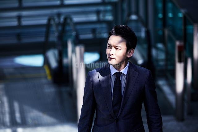 スーツ姿でオフィスエリアを歩くビジネスマンの写真素材 [FYI04269863]
