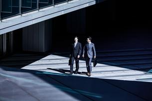 話しながらオフィスエリアを歩くビジネスマンの写真素材 [FYI04269877]