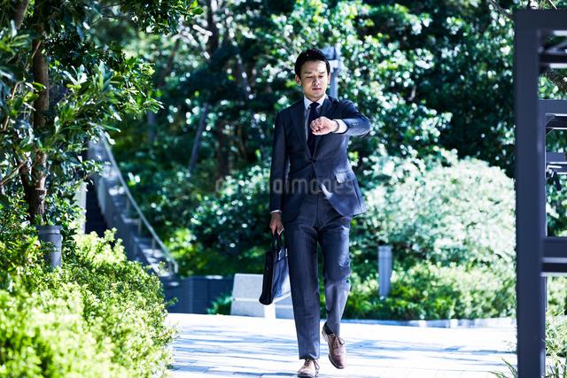 スーツ姿で腕時計を見るビジネスマンの写真素材 [FYI04269890]