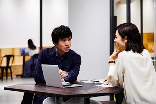 コワーキングスペースでPC見ながら会話する男女の写真素材 [FYI04269918]