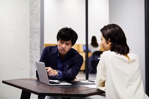コワーキングスペースでPC見ながら会話する男女の写真素材 [FYI04269923]