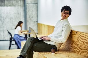 コワーキングスペースでコーヒー飲みながらPCを見る男性の写真素材 [FYI04269931]