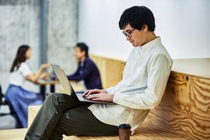 コワーキングスペースでコーヒー飲みながらPCを見る男性の写真素材 [FYI04269932]