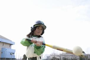 トスバッティングをする野球少女の写真素材 [FYI04271802]