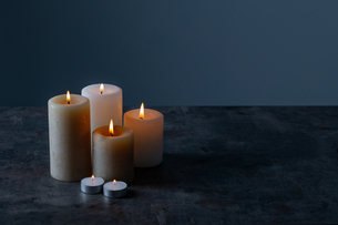 Candle lights in the darkness. Some candles burning in dark background.の写真素材 [FYI04272567]