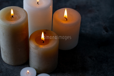 Candle lights in the darkness. Some candles burning in dark background.の写真素材 [FYI04272588]